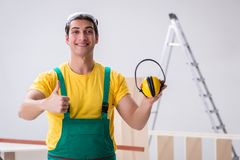 Worker showing the importnace of wearing noise cancelling headph. Ones royalty free stock image