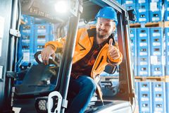 Worker showing thumbs up in logistics delivery center. Successful worker showing thumbs up in logistics delivery center royalty free stock photography