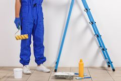 Worker is shown on the waist with a roller on a white background. Worker in blue uniform is shown on the belt with a roller next to the ladder and tools for Stock Photos