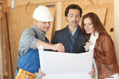 Worker shows house design plans Royalty Free Stock Photography