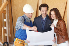 Worker shows house design plans Royalty Free Stock Photos