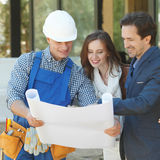 Worker shows house design plans Royalty Free Stock Photo