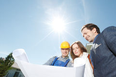 Worker shows house design plans Royalty Free Stock Images