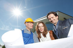 Worker shows house design plans Stock Photos