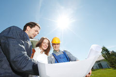 Worker shows house design plans Royalty Free Stock Image