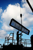 Worker silhouette. Worker guiding a crane-lifted screen for installation in the seawater intake traveling screens stock images