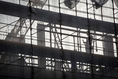 Worker on silhouette. An employee of a construction site taken in backlight through the cloth that covers the building stock images