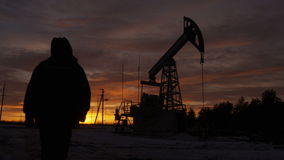 Worker silhouette in hood comes to pumpjack against sunset