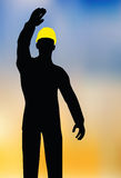 Worker silhouette with yellow protective headgear Stock Photography