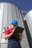 Worker in silo company. Worker in front of the silos Stock Photos