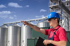 Worker in silo company. Worker in front of the silos Royalty Free Stock Image