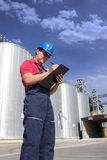 Worker in silo company. Worker in front of the silos checking the delivery of wheat Royalty Free Stock Images