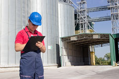 Worker in silo company. Worker in front of the silos checking the delivery of wheat Stock Photo