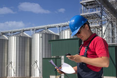 Worker in silo company. Worker in front of the silos using a telephone Stock Photo