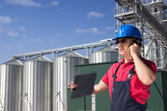 Worker in silo company. Worker in front of the silos using a telephone Royalty Free Stock Image