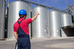 Worker in silo company. Pointing at the elevator tower Royalty Free Stock Images