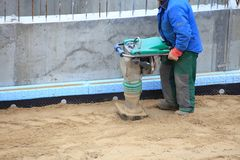 Worker at site working with compress tool Stock Photo