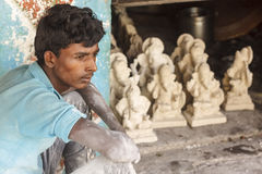 A worker sitting in front of Ganesh idols. A worker in deep thought sitting in front of Ganesh idols that are made with plaster of paris. Ganesh idols are made Stock Image