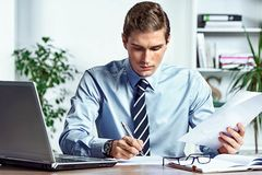 Worker sitting at his desk and checking a documents. Photo of successful man working in the office. Business concept Stock Images
