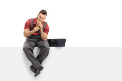 Worker sitting on a panel and eating a sandwich Stock Images