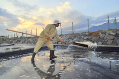 A worker is slapping water out of the salt extracting field in the early morning Stock Photos