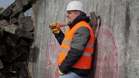 Worker with sledge hammer near the wall stock video footage