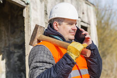 Worker with sledge hammer talking on cell phone Royalty Free Stock Image