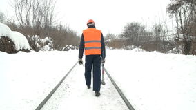 Worker with a sledgehammer goes along the railway stock footage