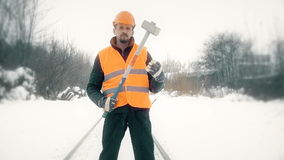 Worker with a sledgehammer goes along the railway stock video