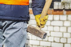 Worker with sledgehammer near to brick wall Royalty Free Stock Images