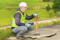 Worker with sledgehammer and tablet PC near broken concrete slabs Stock Photography