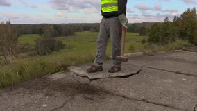 Worker with sledgehammer trying to put back concrete slabs stock video footage