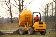 A worker on a small orange dump truck is transporting and emptying the ground forming the landscape at a sports stadium. royalty free stock images