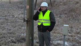 Worker with smartphone at the high-voltage pole stock video footage