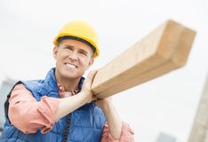 Worker Smiling While Carrying Wooden Plank Stock Photo