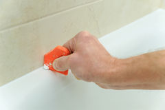 Worker smoothing silicone sealant. Stock Photos