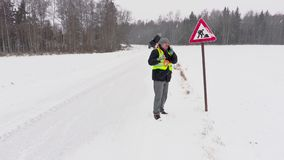 Worker with snow shovel near road sign stock video footage