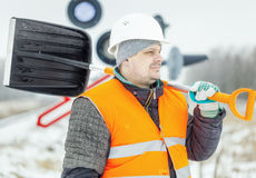 Worker with snow shovel near signal beacons in winter Royalty Free Stock Image