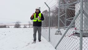 Worker with snow shovel walking near fence and start drink tea stock video