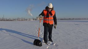 Worker with snow shovel walking and using tablet in factory stock video footage