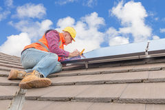 Worker and solar panels Stock Images
