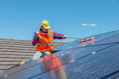Worker and solar panels. Young worker cleaning solar panels on house roof Stock Photography