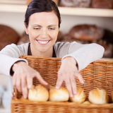 Worker sorting fresh rolls in a bakery Royalty Free Stock Photos