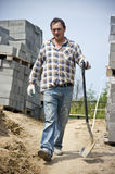 Worker with spade. A worker walking with a spade in his hand. A new house construction site stock photo