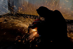 Worker and sparks of bonfire while grinding iron. Silhouettes of Worker and sparks of bonfire while grinding iron Royalty Free Stock Photography