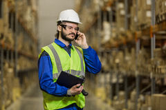 Worker speaking on mobile phone at warehouse Royalty Free Stock Photo