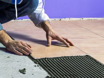 The worker spends construction work, laying tiles on the floor Stock Images