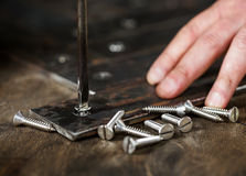 Worker spins screws screwdriver in metal Royalty Free Stock Photography