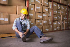 Worker with sprained ankle on floor in warehouse Stock Images