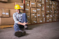 Worker with sprained ankle on floor in warehouse. Male worker sitting with sprained ankle on the floor in warehouse Stock Photos
